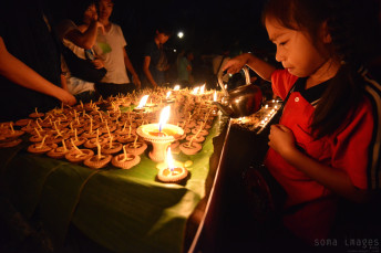 Young girl lighting candles Loy Krathong 2014